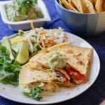simple haddock quesadillas on a blue placement with a side dish of corn chips