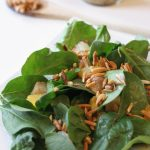 Spinach and Citrus Salad with Sweet and Spicy Almonds with nuts and jar of dressing in the background.