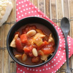 Chicken Chili with White Beans in a brown bowl on a red and white polka dot napkin.