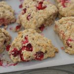 "A close-up of Simple Cranberry and Orange Oatmeal ""Scones"" on a baking sheet with parchment paper."
