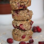 Easy cranberry oatmeal muffins stacked on a white cutting board.