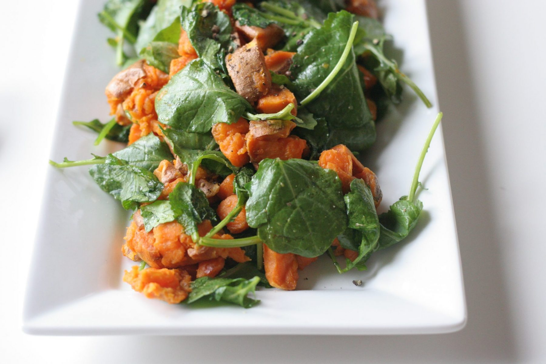 Baked sweet potatoes with wilted baby kale on a plate