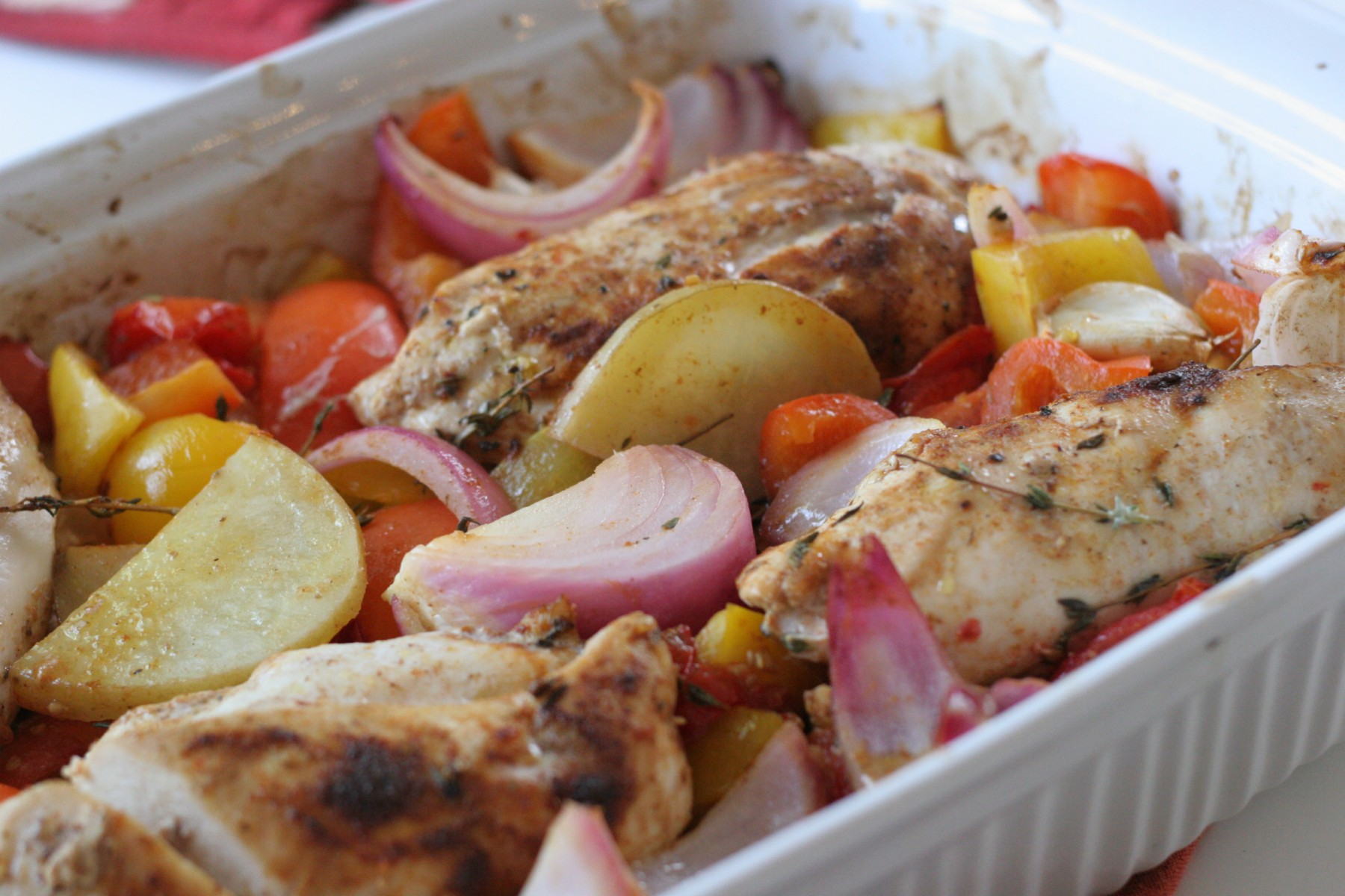 Chicken with Roasted Rainbow vegetables recipe in a white baking dish