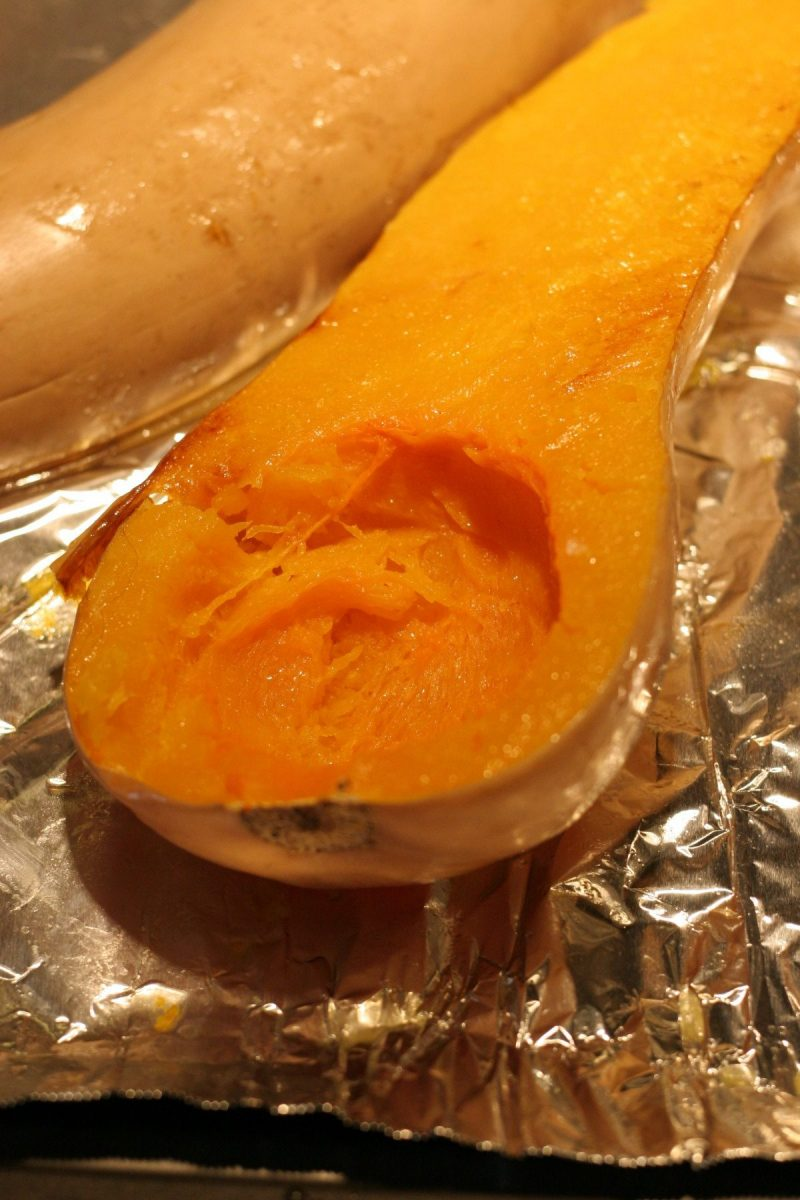 Roasted butternut squash on a tinfoil covered baking sheet.