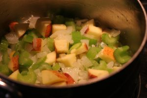 Celery, onion, garlic and apples cooking in a large pot.