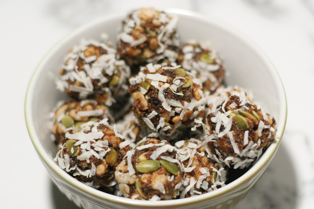 California Prune Energy Bites in a small bowl on a white countertop