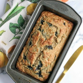 Healthy Banana Bread with White Beans after baking in a loaf pan with a colour tea towel and gold knife
