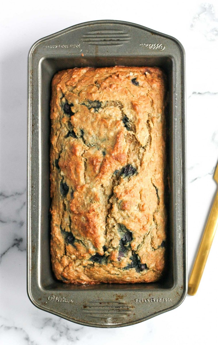 Healthy Banana Bread with White Beans in a loaf pan after baking with a gold knife