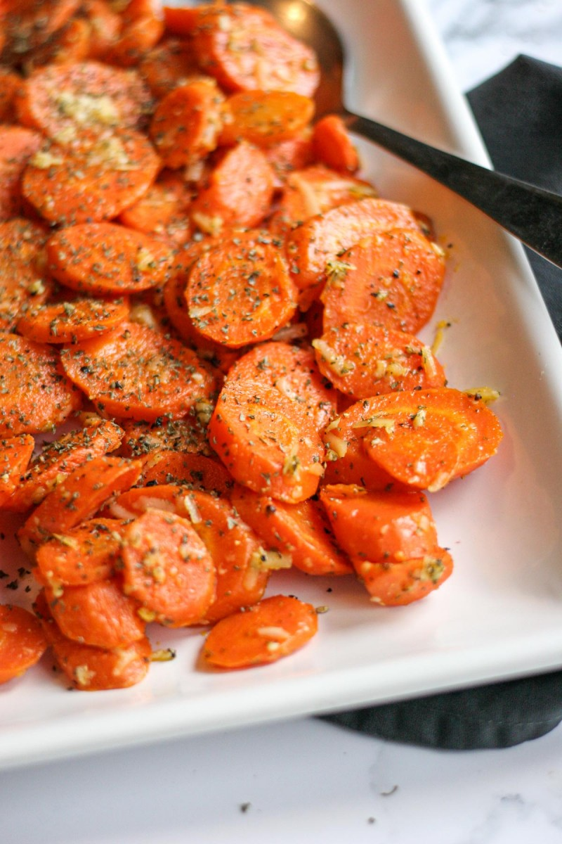 Close up of Easy Roasted Garlic Carrots with Parmesan Cheese on a white platter