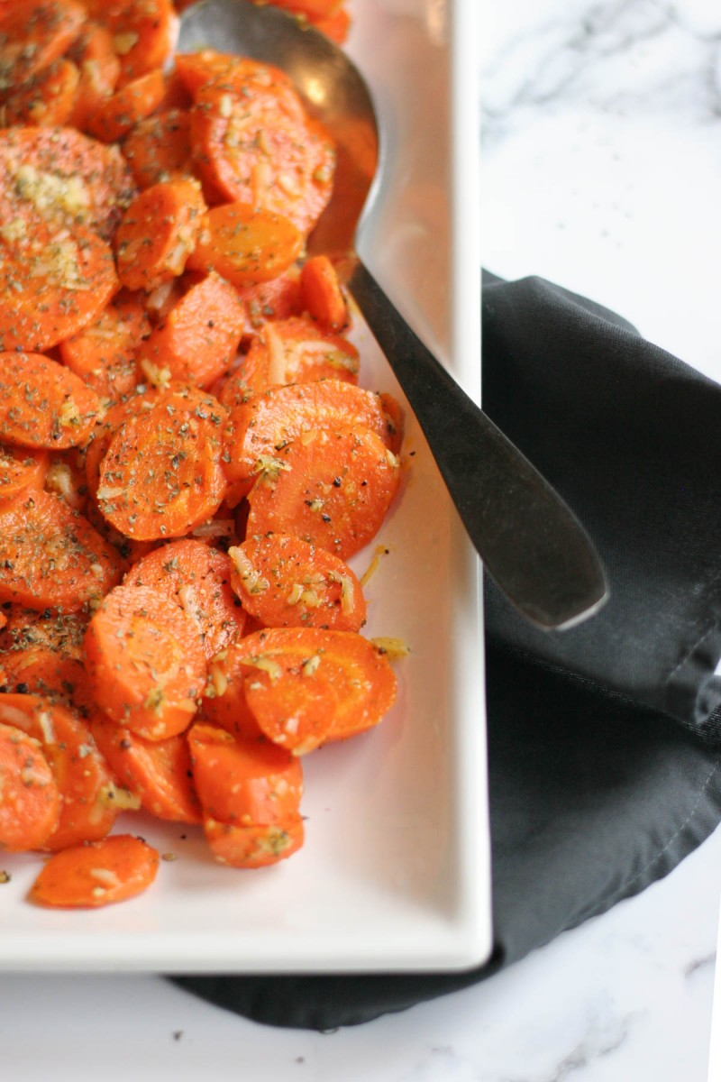 Easy Roasted Garlic Carrots with Parmesan Cheese on a white platter and a grey cloth napkin on the side
