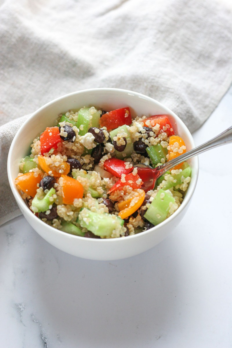 The close up of this Easy Quinoa Salad with Feta in a small white bowl with a fork in the salad