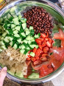 A bowl of black beans, brown rice, tomatoes and cucumber