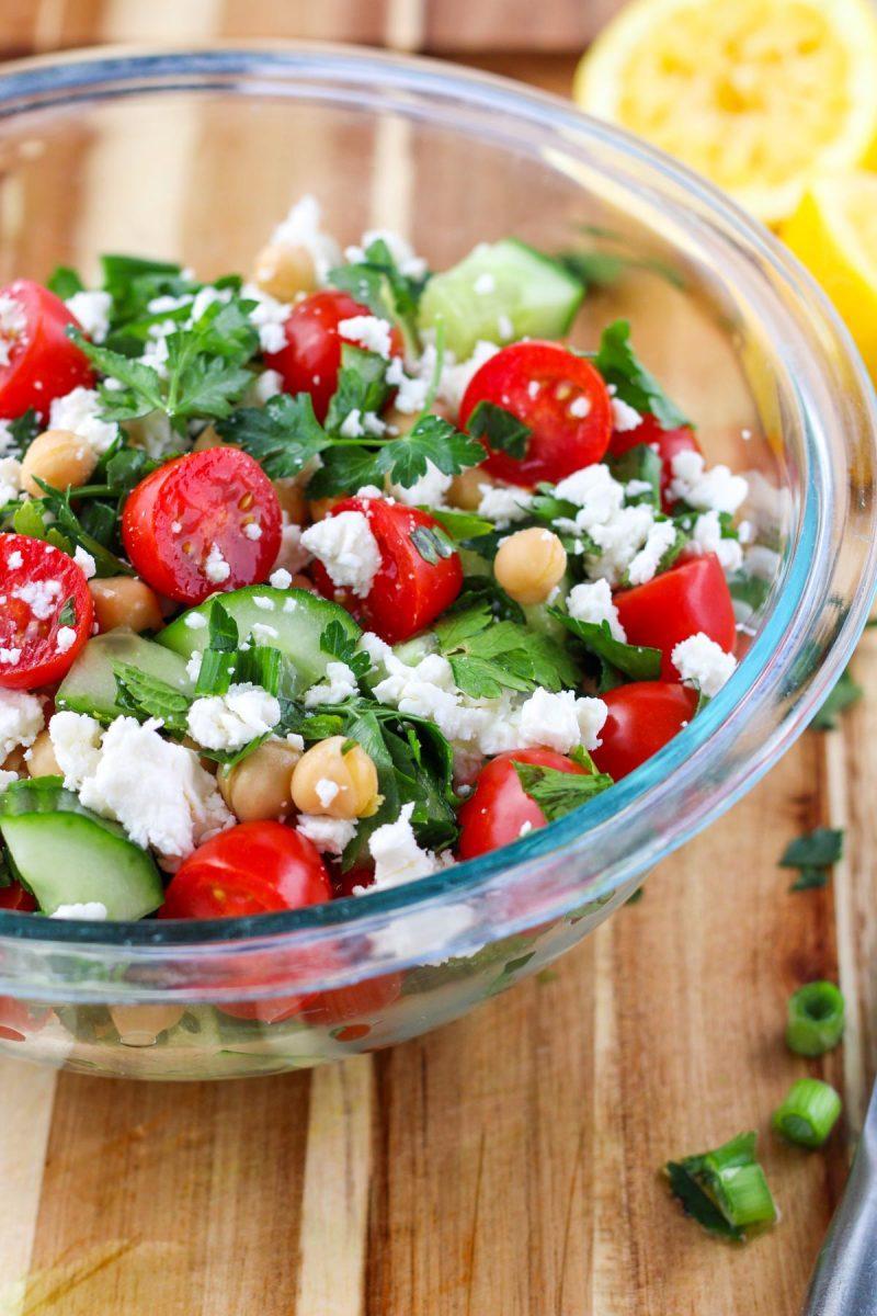 A clear glass bowl filled with Fresh Herb Salad with Chickpeas and Feta