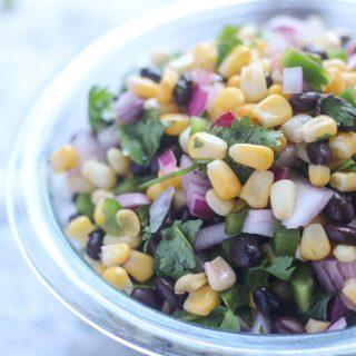 A clear glass bowl of Summer Corn and Black Bean Salsa