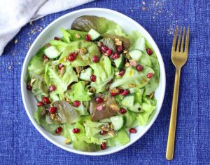 A large white plate filled with Butter Lettuce and Pomegranate Salad on a blue tablecloth with a gold fork beside