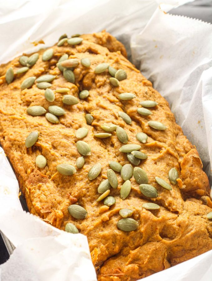 A loaf of pumpkin bread topped with pumpkin seeds