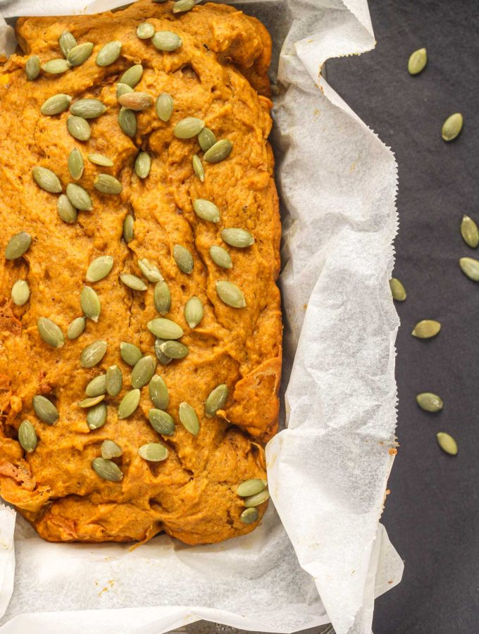 A loaf pan filled with pumpkin bread topped with pumpkin seeds on a grey tablecloth