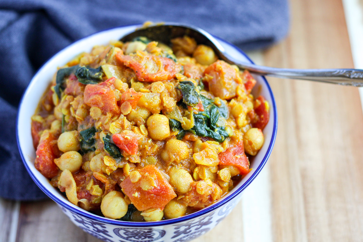 A small blue and white bowl filled with chickpea curry with Spinach on a cutting board