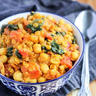 A small blue bowl filled with Red Lentil and Chickpea Curry with Spinach with a silver spoon beside