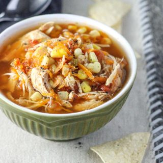 A small green bowl of Healthy Insta Pot Chicken Tortilla Soup on a off-white placemat