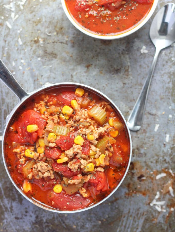 A small pot and a small white bowl of Easy Weeknight Ground Turkey Soup on a baking sheet