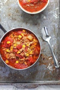 A small pot of turkey soup with corn and tomatoes on a baking sheet