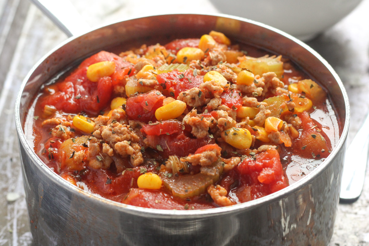 A small soup pot of ground turkey soup with corn and tomatoes