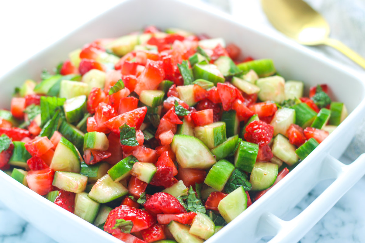 A square white serving dish filled with chopped strawberry Cucumber Salad with Mint