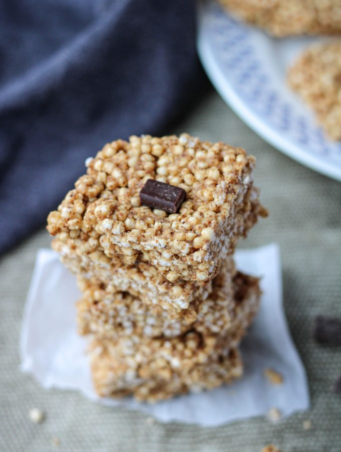 A stack of Puffed Quinoa Bars with Almond Butter on a grey placemat