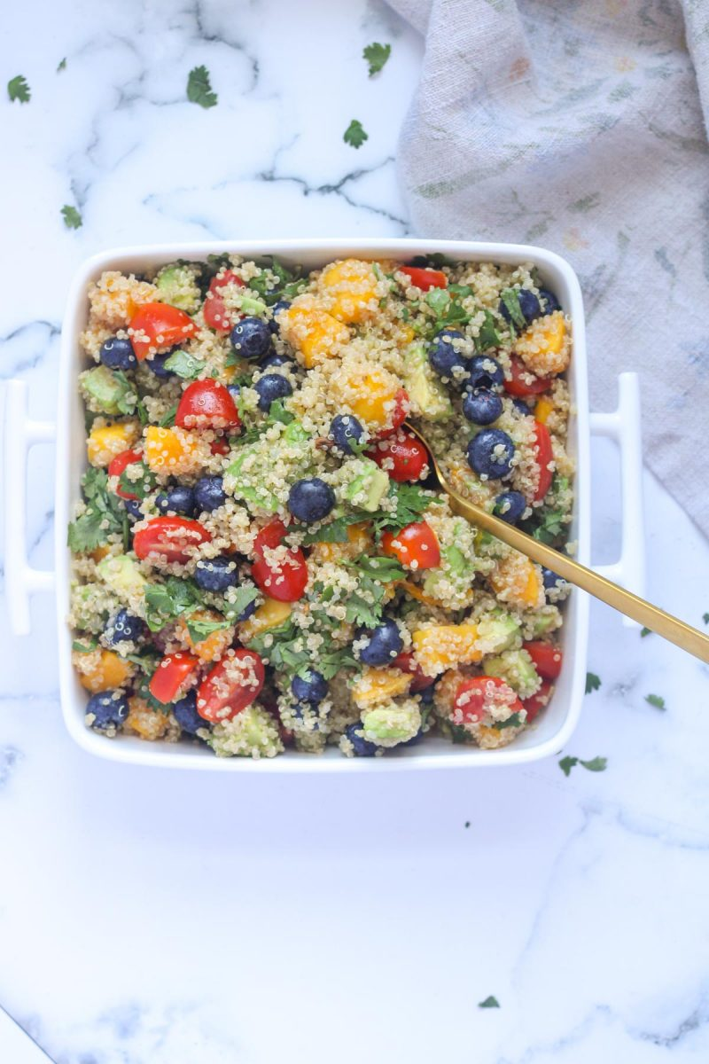 A white and square serving dish filled with Summer Quinoa Salad with Mango and Blueberries