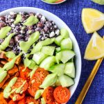 A white bowl filled with black beans, sweet potatoes and veggies on a blue tablecloth and lemon wedges beside