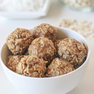 A white bowl of coconut and peanut butter energy bites on a white table