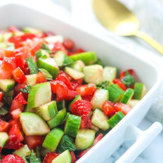 A white dish filled with strawberry Cucumber Salad with Mint with a gold spoon