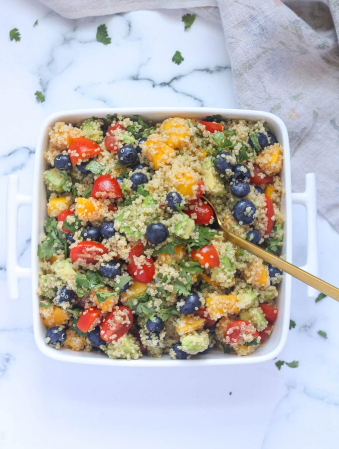 A white dish of Summer Quinoa Salad with Mango and Blueberries with a gold spoon in it