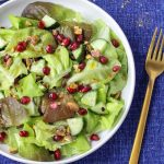 A white plate filled Butter Lettuce and Pomegranate Salad