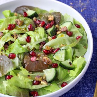A white plate filled with lettuce and Pomegranates with a gold fork beside