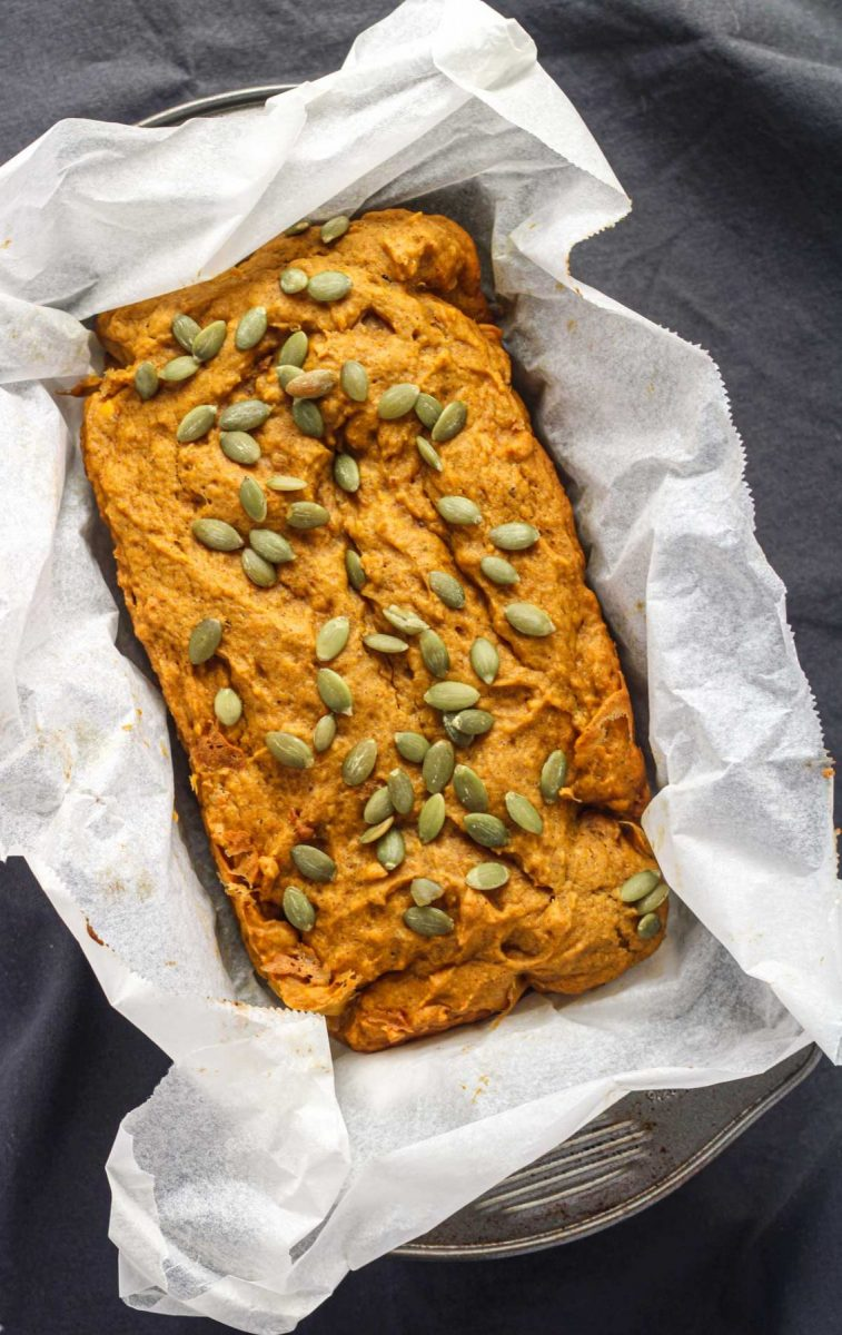 An overhead shot of a pumpkin bread wrapped in parchment paper in a loaf pan on top of a grey tablecloth