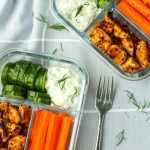 Bento box style glass containers with veggies, chicken and greek dip