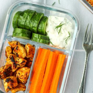 Chicken and veggies with a greek dip in a glass container