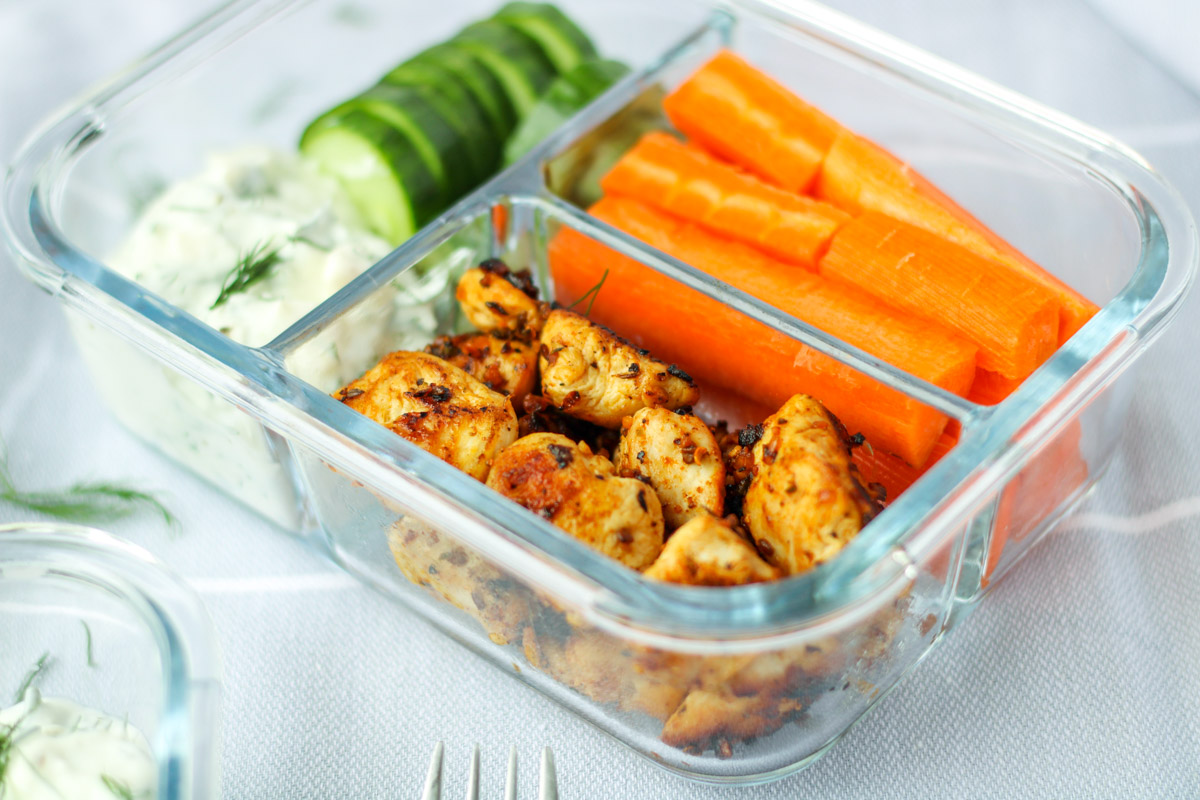 Chicken, carrots and cucumbers with dip in a glass dish