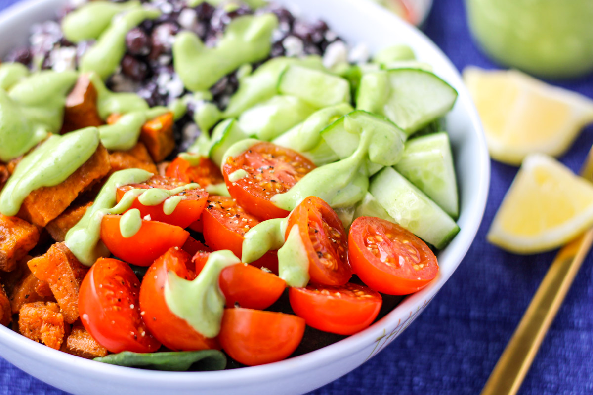 Close up of Powerhouse Veggie Bowls with Whipped Avocado Cilantro Dressing on a blue tablecloth