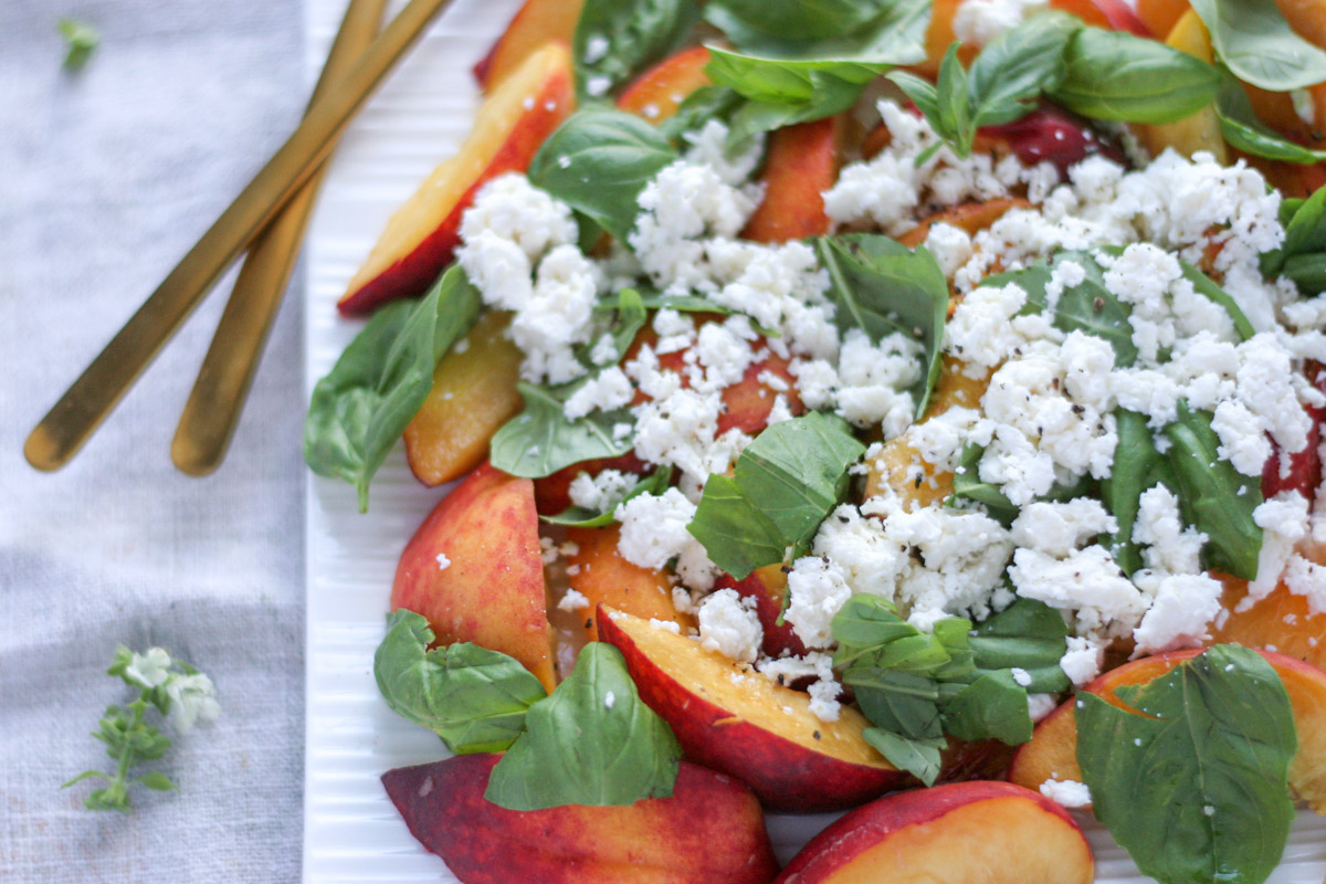 Close up of Summer Peach Basil Salad with Feta on a white platter with gold cutlery