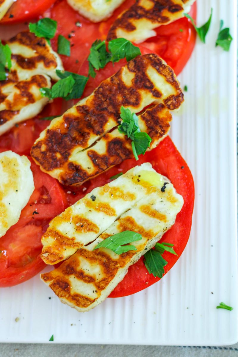 Close up of grilled Halloumi on a tomato slices with Parsley