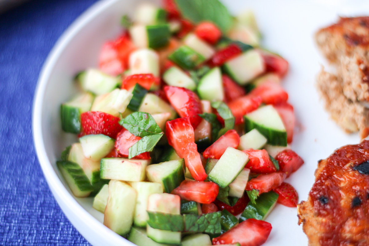 Close up shot of strawberry cucumber salad on a white plate