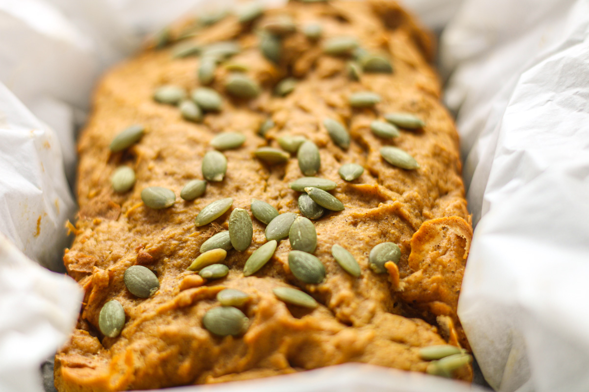 Closeup shot of pumpkin bread topped with pepitas
