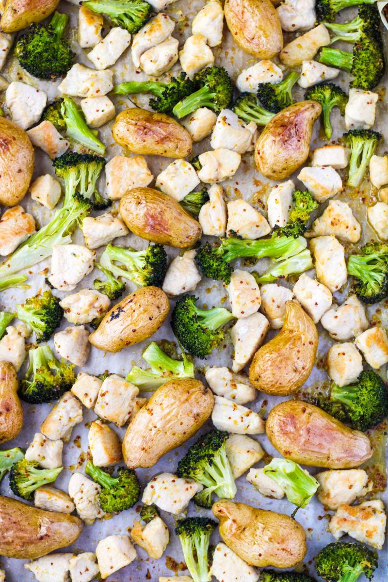 Cut pieces of chicken, broccoli and potatoes on a baking sheet