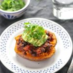 Easy Black Bean Stuffed Sweet Potatoes with Avocado on a white plate