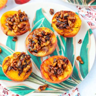 Easy Gluten Free Grilled Peaches with Walnuts on a plate with leaves