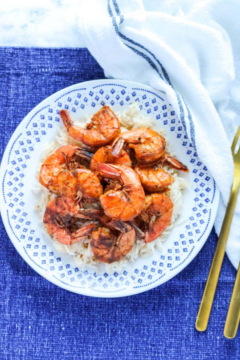 Easy Sweet and Spicy Shrimp on a white plate and blue placemat