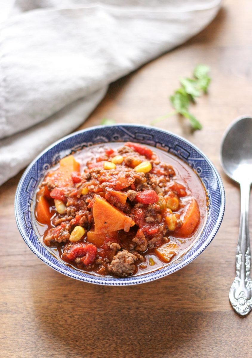 Easy Weeknight Hamburger Soup with Sweet Potatoes in a blue bowl on a brown wood table